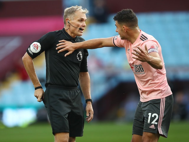 Sheffield United's John Egan protests to referee Graham Scott after being sent off against Aston Villa in September 2020