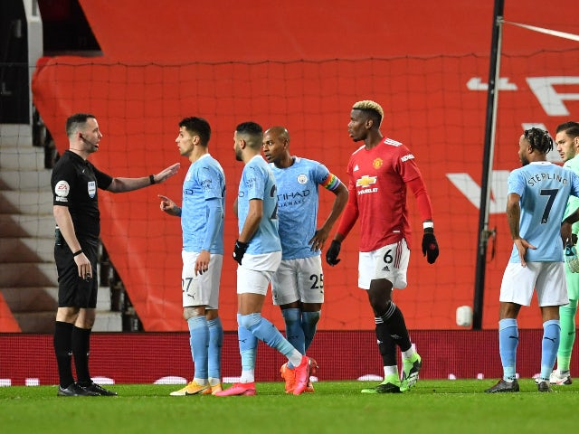 Manchester City's Joao Cancelo and teammates remonstrate with referee Chris Kavanagh against Manchester United in the Premier League on December 12, 2020