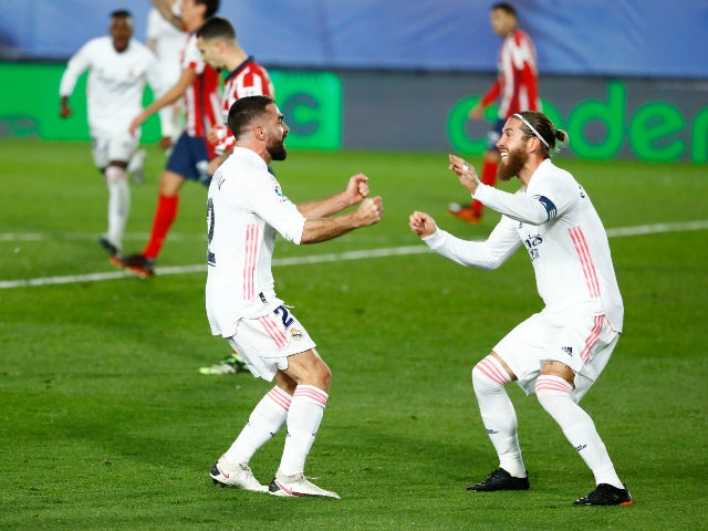 Real Madrid's Dani Carvajal celebrates with Sergio Ramos after Atletico Madrid's Jan Oblak scored an own goal in La Liga on December 12, 2020