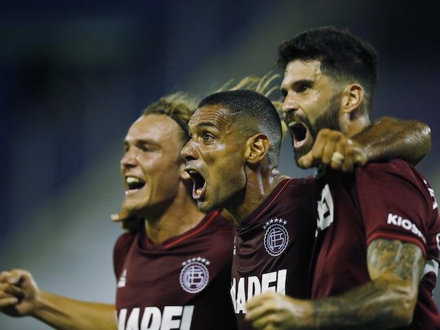 Lanus' Jose Sand celebrates scoring their first goal with teammates on January 6, 2021
