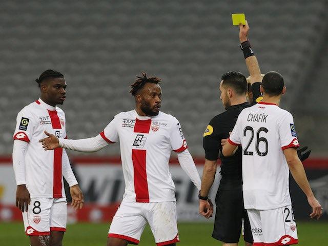 Dijon's Ngonda Muzinga is shown a yellow card by referee Jeremie Pignard in January 2021