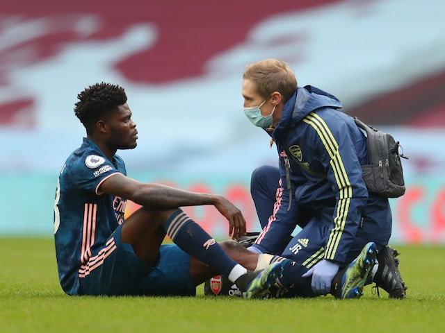Arsenal midfielder Thomas Partey receives treatment for an injury in February 2021