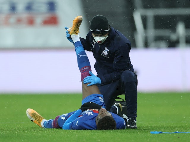 Crystal Palace's Wilfried Zaha receives medical attention after sustaining an injury in February 2021
