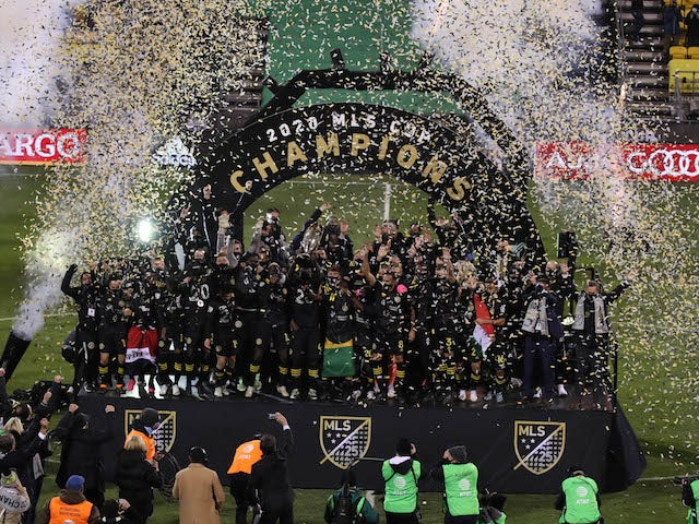Columbus Crew players celebrate on stage with the MLS Cup championship trophy after defeating the Seattle Sounders in the 2020 MLS Cup Final at MAPFRE Stadium in December 2020