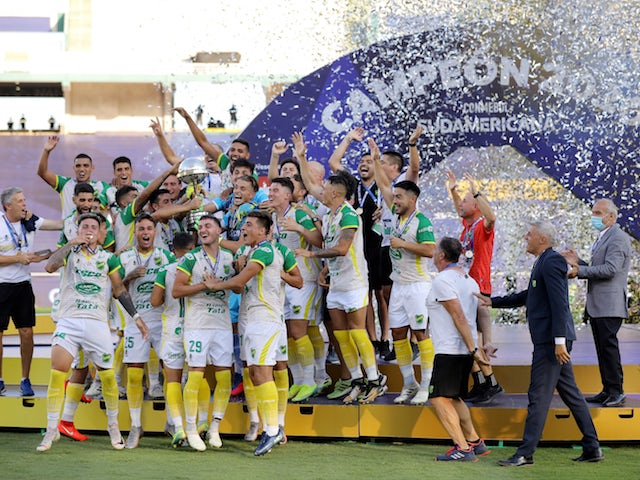 Defensa y Justicia players celebrate with the trophy after winning the Copa Sudamericana in January 2021