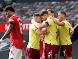 James Tarkowski celebrates scoring Burnley's first goal with teammates against Manchester United in the Premier League on April 18, 2021