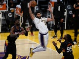 Los Angeles Lakers forward Anthony Davis grabs a rebound in front of Phoenix Suns center Deandre Ayton on May 10, 2021