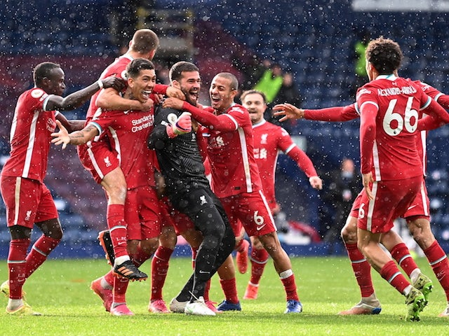 Liverpool's Alisson celebrates scoring their second goal with teammates on May 16, 2021