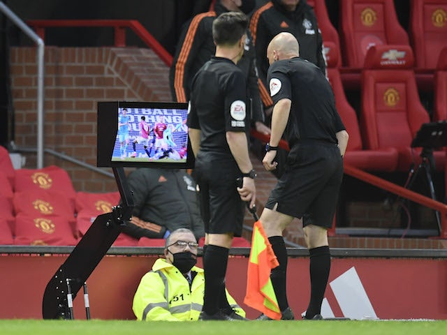 Referee Anthony Taylor consults the pitchside VAR during the Premier League clash between Manchester United and Liverpool on May 13, 2021