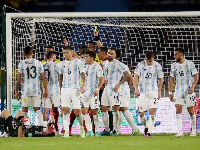 Colombia's Yerry Mina is shown a yellow card by referee Roberto Tobar as Argentina's Emiliano Martinez sustains an injury on June 8, 2021