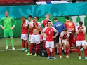 Denmark's Thomas Delaney, Andreas Christensen and teammates stand in front of Christian Eriksen as he receives medical attention at Euro 2020 on June 12, 2021