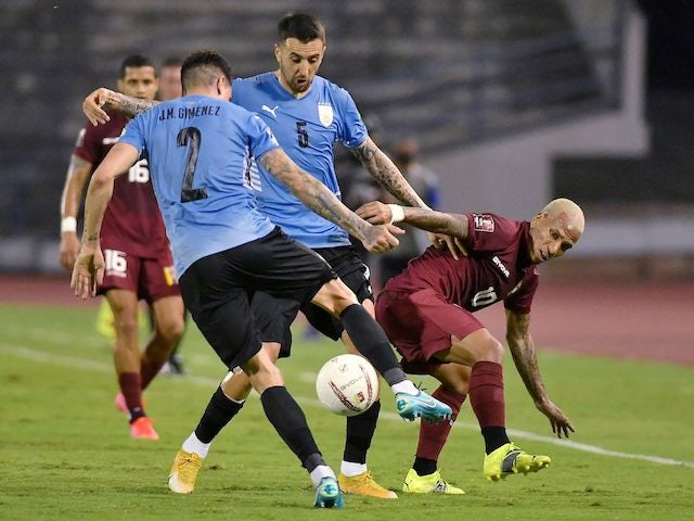 Uruguay's Jose Gimenez and Matias Vecino in action with Venezuela's Romulo Otero on June 8, 2021