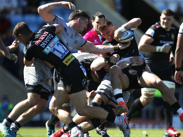 Exeter Chiefs' Henry Slade in action with Sale Sharks' Tom Curry and Jean-Luc du Preez on June 12, 2021