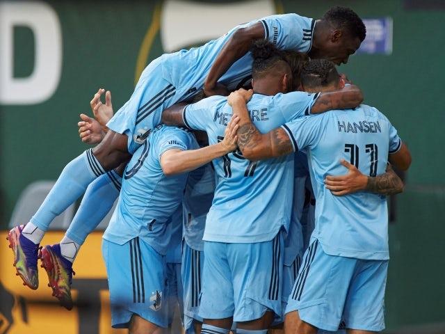 Minnesota United midfielder Adrien Hunou celebrates with teammates after scoring a goal on June 27, 2021