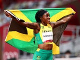 Elaine Thompson-Herah of Jamaica poses with her national flag after winning gold on August 3, 2021