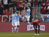 New York City FC forward Valentin Castellanos (11) celebrates a goal by forward Santiago Rodriguez (not pictured) against Toronto FC with defender Malte Amundsen (12) and forward Thiago (8) during the first half at BMO Field on August 7, 2021