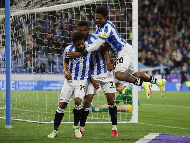 Huddersfield Town players celebrate after Preston North End's Sepp Van Den Berg scored an own goal in the Championship on August 17, 2021