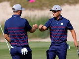 Team USA's Xander Schauffele and Dustin Johnson react during the Ryder Cup on September 24, 2021