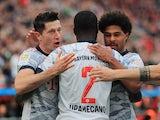 Bayern Munich's Robert Lewandowski celebrates scoring their first goal with Dayot Upamecano and Serge Gnabry on October 17, 2021