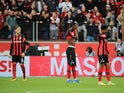 Bayer Leverkusen's Panagiotis Retsos, Odilon Kossounou and Amine Adli look dejected during the match on October 17, 2021