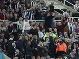 Newcastle United fans attract the attention of the officials to a medical emergency in the stands on October 17, 2021