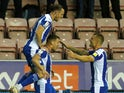 Wigan Athletic's Charlie Wyke celebrates scoring their first goal with teammates on October 19, 2021