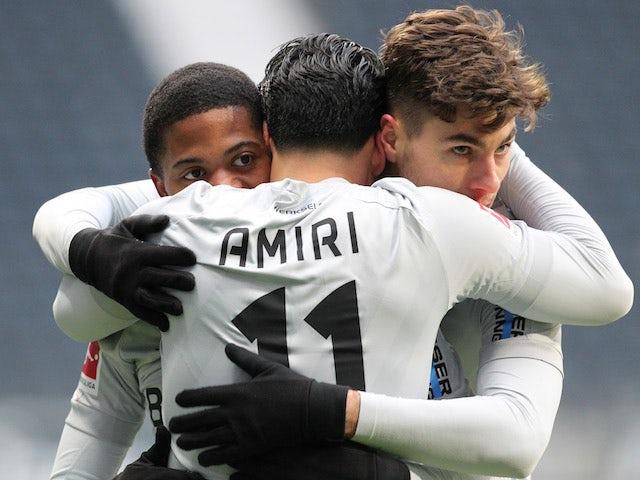 Bayer Leverkusen's Nadiem Amiri celebrates with teammates after scoring their first goal on January 2, 2021